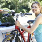 Mature Female Cyclist Taking Mountain Bike From Rack On Car