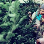 Woman with daughter buying Christmas tree in market