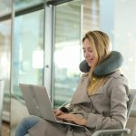 Female person sitting in waiting room with laptop near valise, using neck pillow