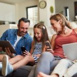 Shot of a happy young family using wireless devices on the sofa at home